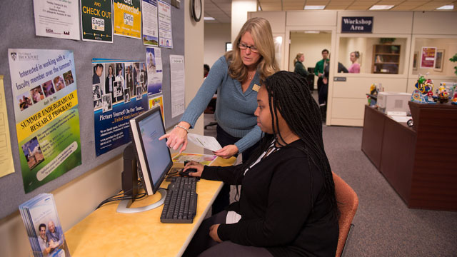 Picture of Financial Aid office, staff member assisting a student